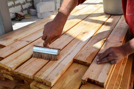 Photo de l'application d'une protection sur une poutre en bois